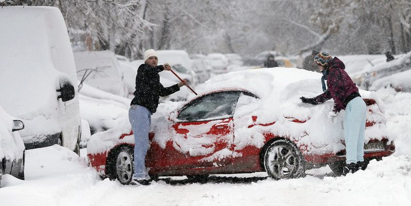 epa05106925 A Romanian couple cleans the snow over their car, which was moved in the middle of the road to have more room for the operation, in Bucharest, Romania, 17 January 2016. Snowfalls and strong blizzards severely affected the traffic in south-eastern Romania. The A2 motorway and 16 national roads were temporarily closed while three international flights and 29 railway regional trains were canceled. Authorities decided that all schools will be closed in the capital and other six counties in southeast Romania on 18 January. EPA/ROBERT GHEMENT