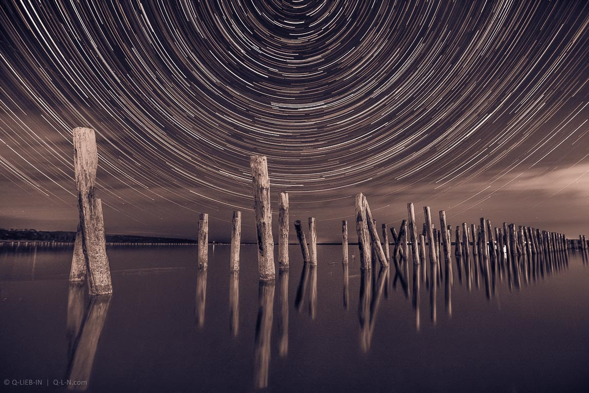 Unusual pillars in the water at night on a background star trails in the sky