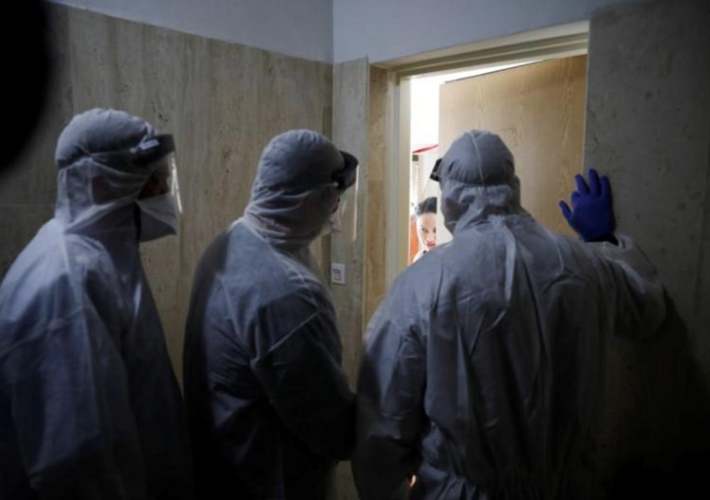 На фото: инспекторы Минздрава говорят с женщиной, которая находится в самоизоляции. Hadera, Israel March 16, 2020 REUTERS / Ronen Zvulun