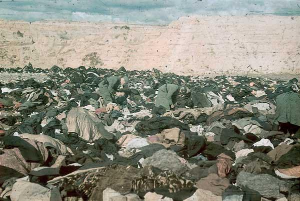 Солдаты роются в вещах расстрелянных евреев. Перед смертью их заставляли раздеться.