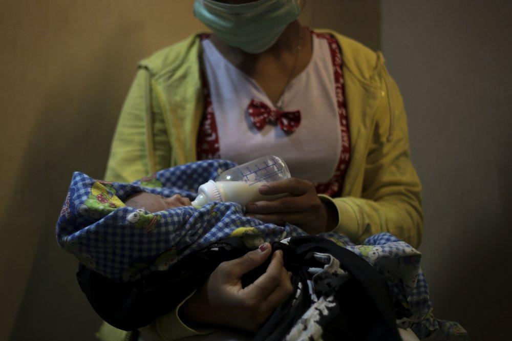 Мать-подросток дает бутылочку своему двухнедельному ребенку, который, по ее словам, родился в результате изнасилования на Суматре. Она начала работать на плантации маленькой девочкой, чтобы помочь своей семье выжить, никогда не ходила в школу и не умеет ни читать, ни писать.