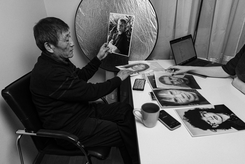 """Цой держит фотографию Виталия Шумейко. Мужчина рассказывает, что за прошедшие годы несколько знакомых Виталия находили его в соцсетях: «Многие из них говорили """"знали, что наш бывший одноклассник женился на кореянке, а теперь мы узнали, что у вас такая беда. Оказывается, вы папа его бывшей жены"""". Писали в основном о житейском, что не ожидали от Виталика такого»."""