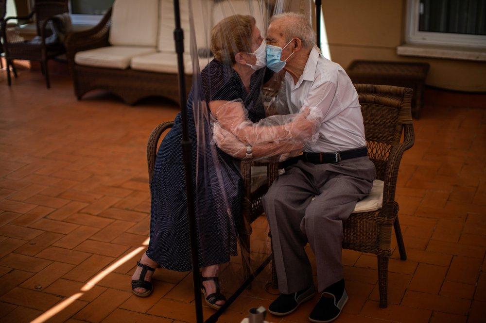 81-летняя Августина Канамеро и 84-летний Паскуаль Перес целуются через экран из пластиковой пленки в доме престарелых Барселоны.