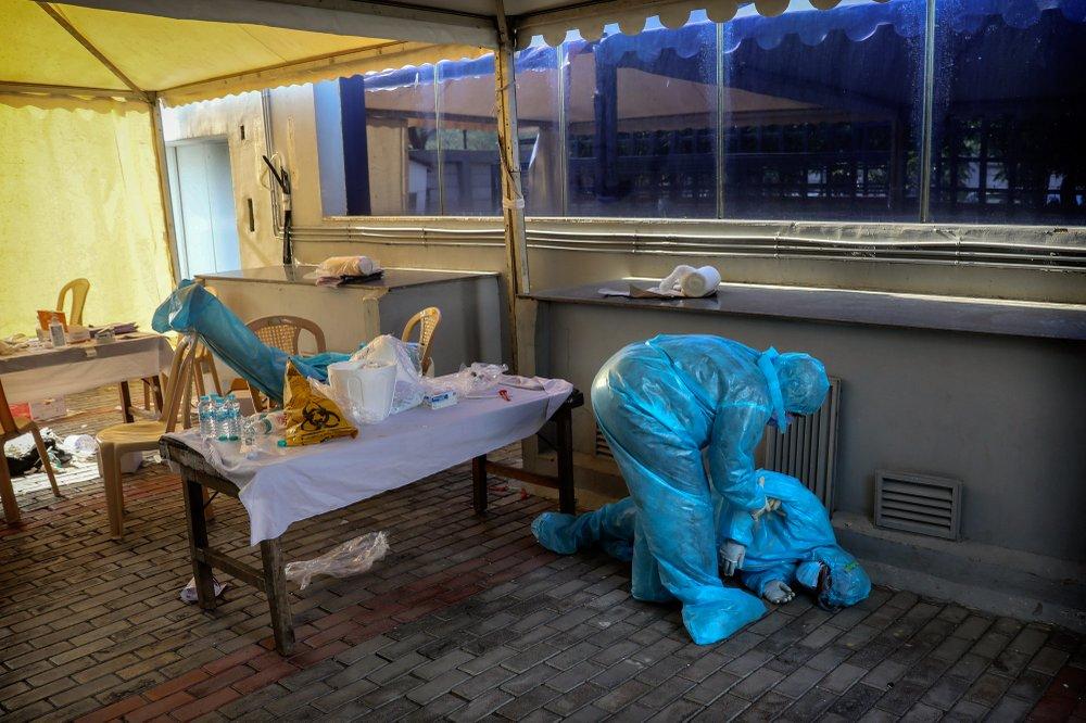 Медицинский работник помогает своей коллеге, которая упала в обморок в лагере для тестирования на COVID-19. Нью-Дели, Индия.