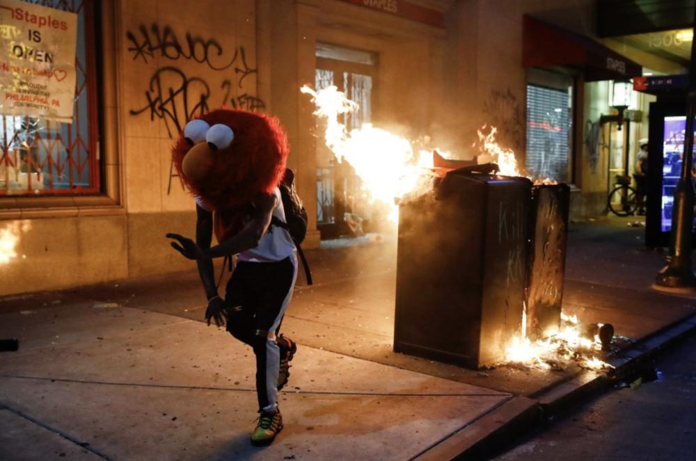 Протестующий бежит в маске Элмо из «Улицы Сезам». Акция из-за смерти Джорджа Флойда.