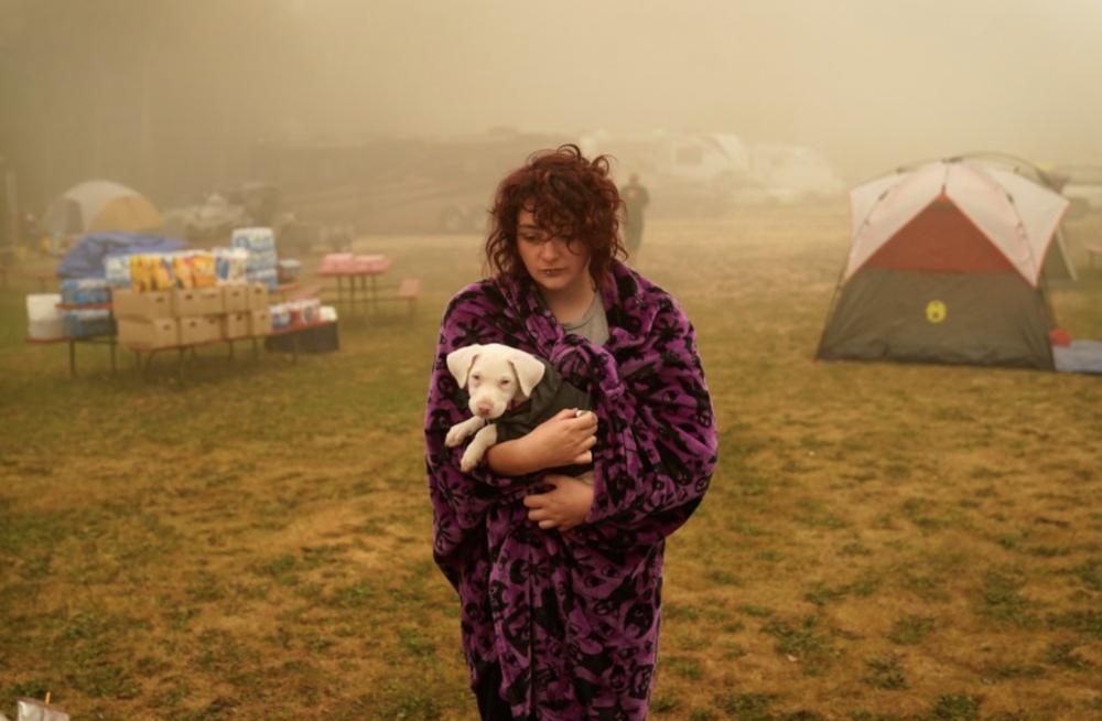 Шаянн Саммерс держит свою собаку Тоф. Девушка провела несколько дней в палатке в центре эвакуации, она приехала из штата Орегон, где бушевали пожары.