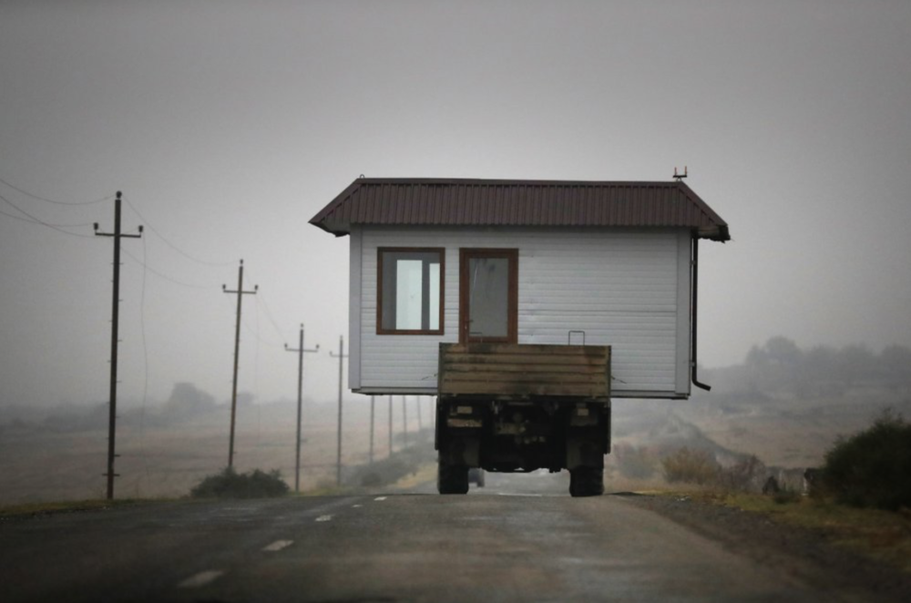 Семья едет с небольшим домом на грузовике — они покидают свою родную деревню в Нагорном Карабахе.