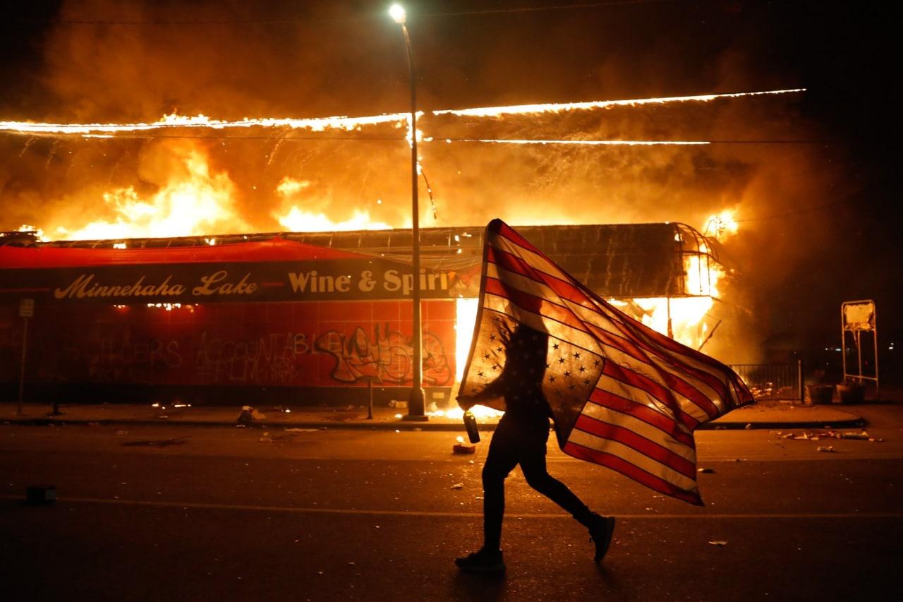 Мужчина несет флаг США вверх ногами на акции протеста из-за смерти Джорджа Флойда.