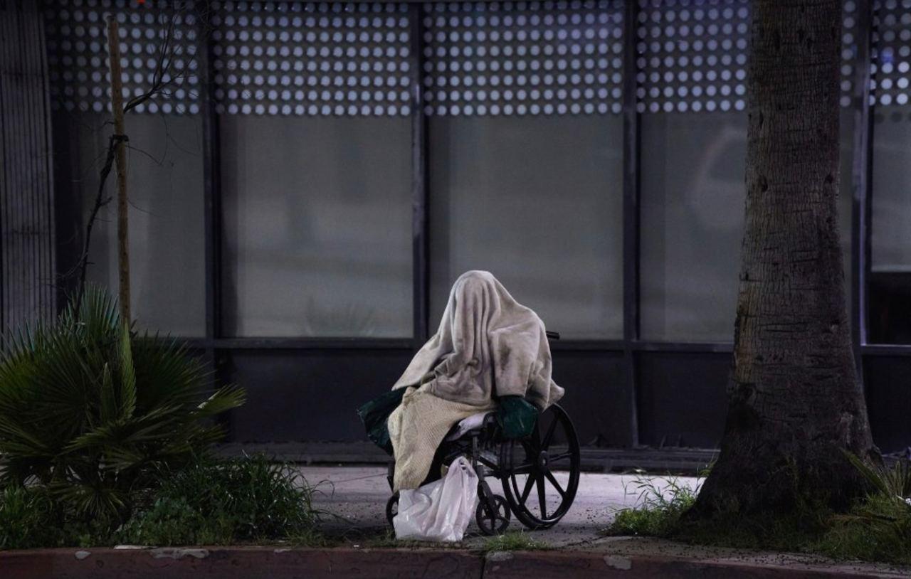 Бездомный сидит в инвалидном кресле в дождливую погоду на бульваре Сансет.