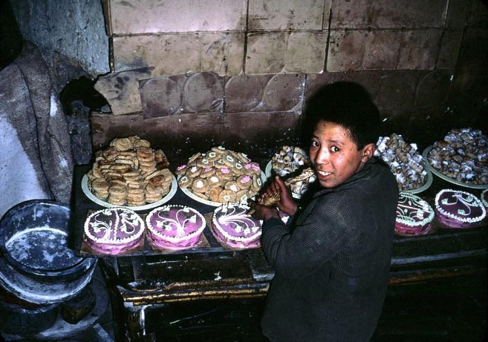 Мальчик украшает торты, печенье и другие сладости.
